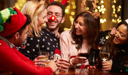 A group of young people in Christmas jumpers laughing as tehy hold glasses of wine.